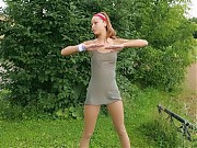 Slender gal in tights limbers up outdoors