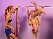 Nude gymnast working out on horizontal bar