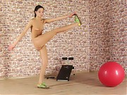 Fitness and gymnastics workouts by a slim brune ba...
